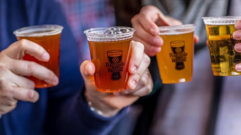 Raising beer glasses with riverside craft beer logos