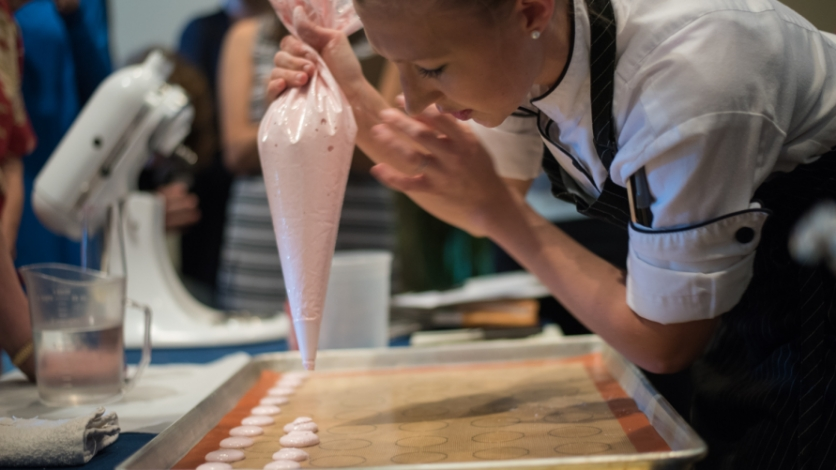 pastry chef rebecca reed piping macarons onto a silpat mat at matthews restaurant in jacksonville florida