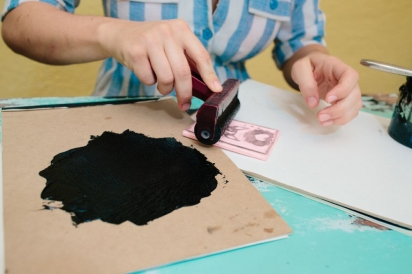 rolling ink from a brayer onto a diy linoleum stamp