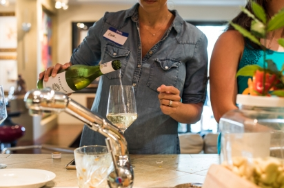 Woman pouring wine at counter