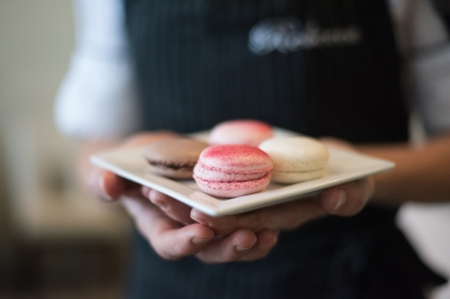 one pink macaron held in hands on a white plate at matthews restaurant in jacksonville florida