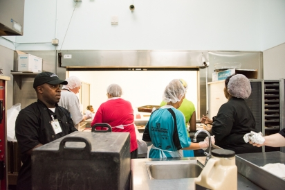Volunteers from the shelter line up to serve food