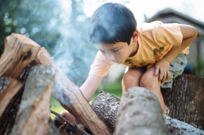 boy lighting campfire