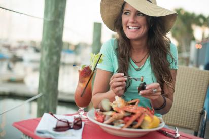 Girl eating seafood on the dock