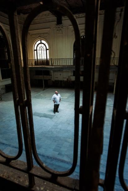 Chef Scott Schwartz between balcony rails in the Marble Bank Building Downtown Jacksonville