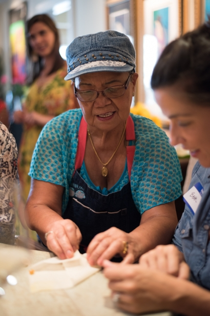 Cely teaching students to roll lumpia