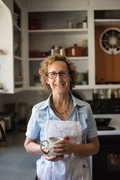 Lauren Titus editor of Edible Northeast Florida magazine stands in an apron in a kitchen