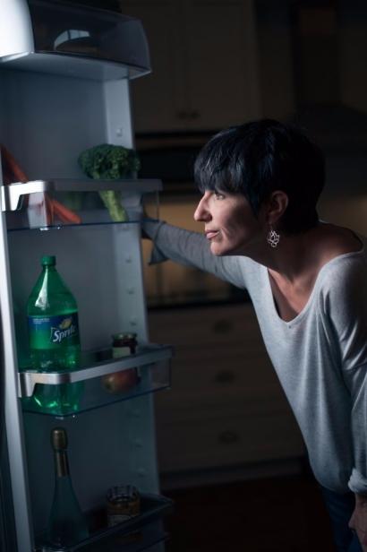 Woman standing by fridge choosing food