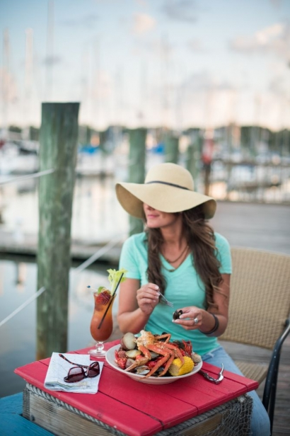woman enjoying a meal by the water