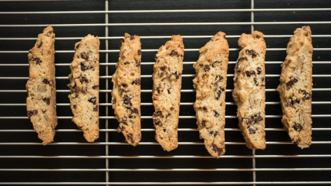 Chocolate Chip walnut biscotti on a baking rack with black background