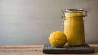 Meyer lemon curd in a jar with a lemon on a wood table