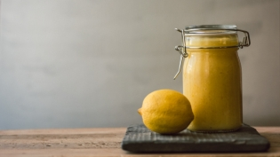 Meyer lemon curd in a jar with a lemon on a wood table