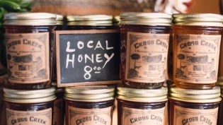 cross creek honey jars and sign at community loaves in jacksonville