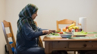 Refugee mother at the table cutting vegetables for her familys lunch in jacksonville Florida