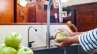 Washing apples in galley sink on sailboat