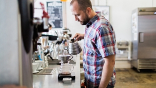 zach burnett pours water over coffee at bold bean roasters in jacksonville florida