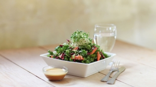 Kale salad with citrus dressing on wood table