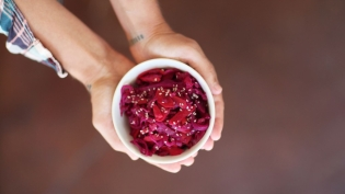 beet kimchi in white bowl in palm of hands
