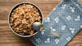 bowl of granola with spoon on wooden table and blue napkin