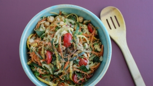 Vegan Harvest Slaw with Tahini dressing in a blue bowl on a purple background