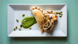 Kale and Sweet Potato empanadas with pumpkin seed chimichurri on a plate